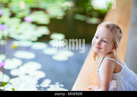 Adorable little girl sitting near water lily pond - Stock Photo