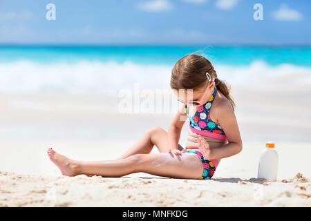 Adorable little girl at tropical beach applying sunblock cream - Stock Photo