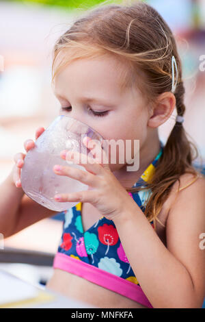 Adorable little girl drinking water from a glass