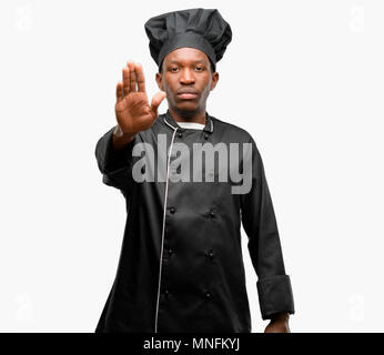 Young black cook wearing chef hat annoyed with bad attitude making stop sign with hand, saying no, expressing security, defense or restriction, maybe  - Stock Photo