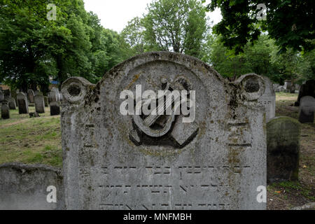 London UK. Close up photo of tombstone at the historic Jewish cemetery at Brady Street, Whitechapel, East London, showing lyre / harp symbol. - Stock Photo