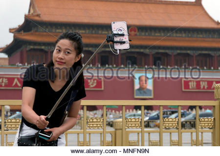 Young Chinese woman taking selfie at the entrance gate of the Forbidden City in Tiananmen Square, Beijing, China, Asia - Stock Photo