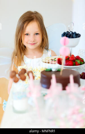 Adorable little fairy girl on a birthday party in front of dessert table - Stock Photo
