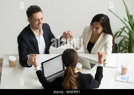 Business team meditating together holding hands - Stock Photo