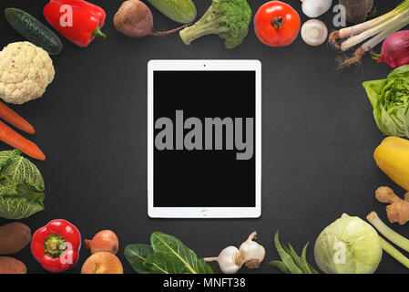 Tablet with blank screen surrounded with vegetables. - Stock Photo