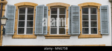close up view of three windows with wooden window shutters in blue - Stock Photo