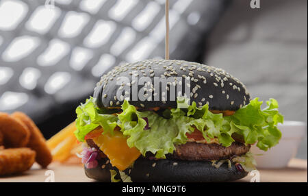 Black burger on a wooden background with potatoes and sauce - Stock Photo