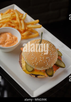 Burger on a plate with fried potatoes and sauce - Stock Photo