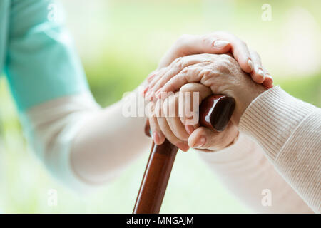 Nurse in apron comforting elder lady by touching her hands - Stock Photo