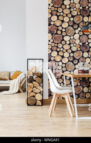 Warm dining room decor inspired by autumn woodland with simple furniture, firewood and logs wallpaper - Stock Photo