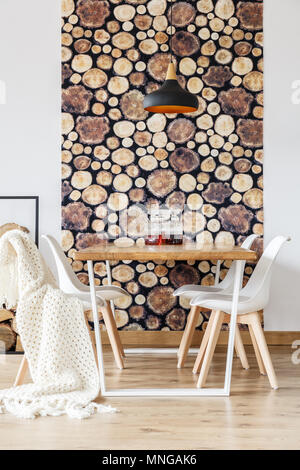 Soft textiles and log wallpaper in impressive dining room with scandinavian decor, white chairs and wooden communal table - Stock Photo