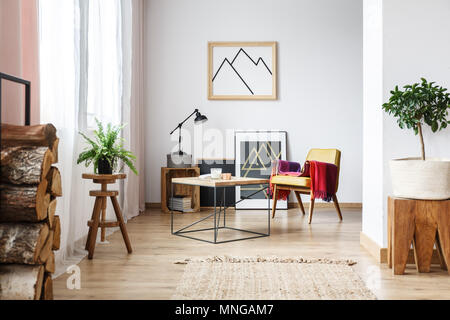 Simple wooden design in open plan, bright living room interior with armchair, minimalist poster and firewood - Stock Photo