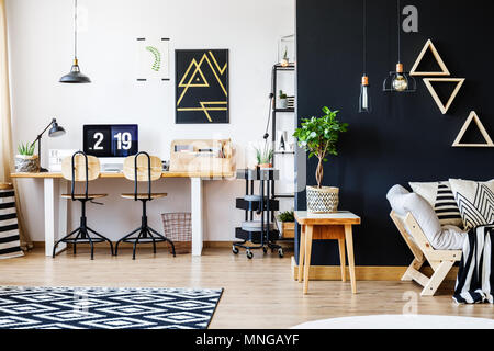 Stylish black and white nordic style open space apartment with wooden furniture, office workspace with desk and computer, and spacious living room wit - Stock Photo