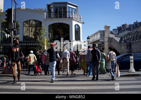 A busy Boulevard Barbès, Paris, France, with Brasserie Barbes in background - people crossing the road - Stock Photo