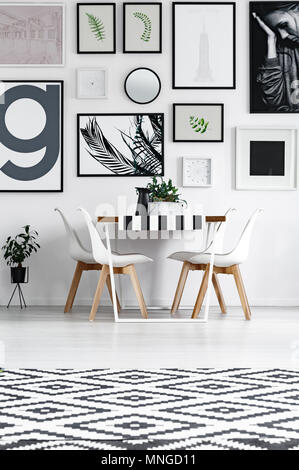 Dining room in black and white patterns with posters on the wall - Stock Photo