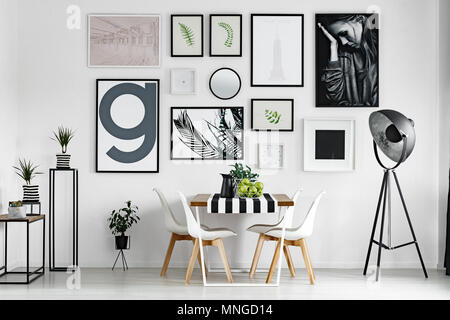 Wooden dining table with tablecloth by white wall with pictures - Stock Photo