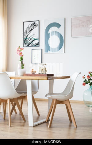 Bright wooden table with decorations in dining room - Stock Photo