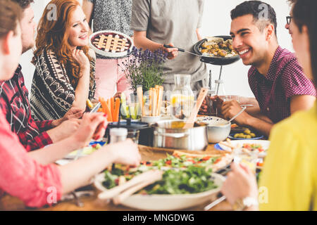 Healthy smiling friends enjoy meeting at communal table with hummus, falafel and vegetables - Stock Photo