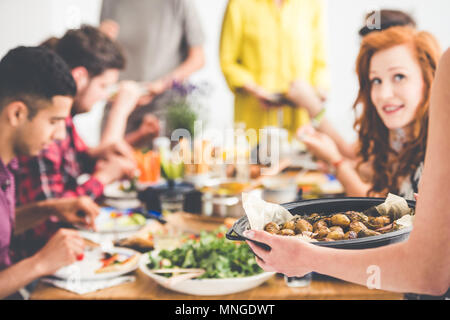 Vegetarian shares baked potatoes with vegan friends during vege meeting at home - Stock Photo