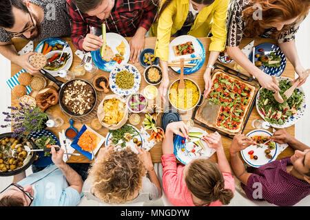 Vegetarians enjoy tasty dish which consists of hummus, salad, bulgur groats and vege pizza - Stock Photo