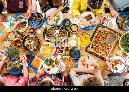 Veggie meeting of friends at communal table in restaurant with raw healthy food - Stock Photo