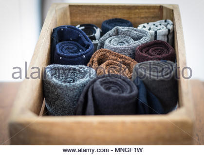 Rolled up socks neatly stored on a wooden box. - Stock Photo