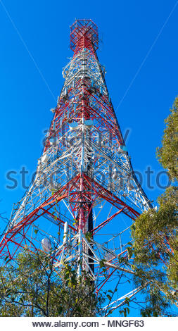 Telecommunications tower with communication devices and equipment installed. - Stock Photo