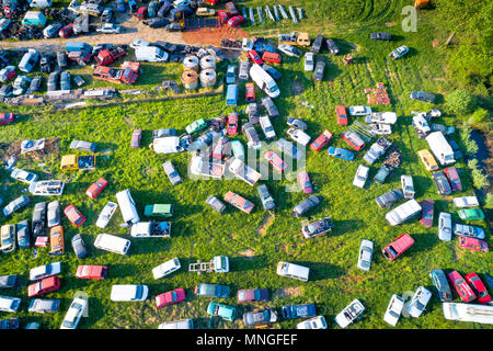 Car wrecks on meadow aerial view, ecological problem - Stock Photo