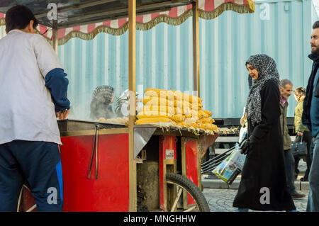 Istanbul, Turkey - January 06, 2018: Man selling boiled and roasted corn in touristic Eminonu district of Istanbul city, Turkey - Stock Photo