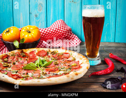 delicious pizza, glass of beer vegetables and spices on wooden table. - Stock Photo