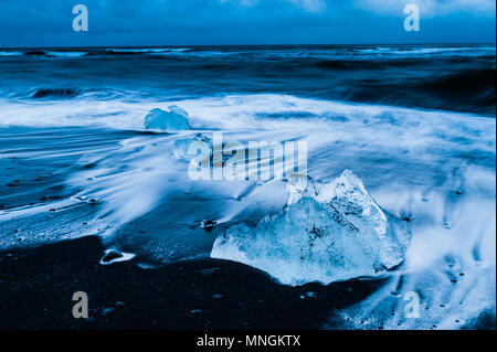 Ice rocks washed by the upcoming surf of the atlantic ocean at black volcanic sand at diamond beach, Iceland april 2018 - Stock Photo