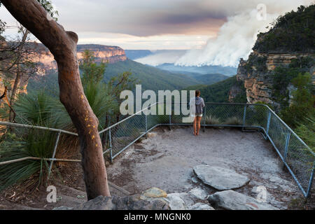 Girl at a bushwalking lookout with a view over a remote bushfire and smoke in the Blue Mountains, New South Wales, Australia. - Stock Photo