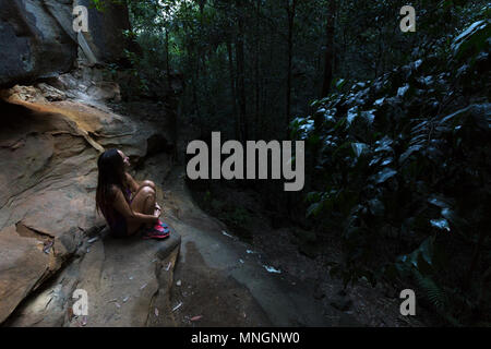 A pretty, beautiful girl hugs her knees in a dark, dimly lit forest in the Blue Mountains, Australia. - Stock Photo