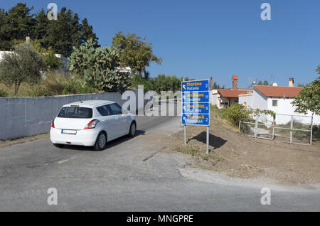 Road sign with names of settlements in the English and Greek languages and the direction of the movement on the island Rhodes (Greece). - Stock Photo