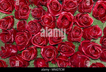Red roses made of wax on moss - Stock Photo
