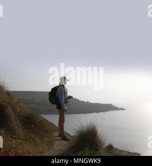 Young woman standing looking out to sea, she is wearing shorts a rucksack and peak cap. She is high up looking down - Stock Photo