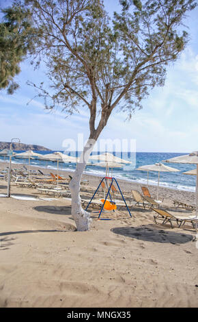 Sunbeds and umbrellas on the beach of Kalamaki in southern crete - Stock Photo