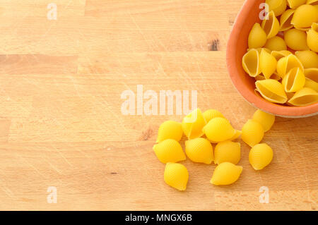 conchigliette, italian type of pasta, made like a seashell, overturned from a terracotta pots, on a wooden board, view from above with large copy spac - Stock Photo