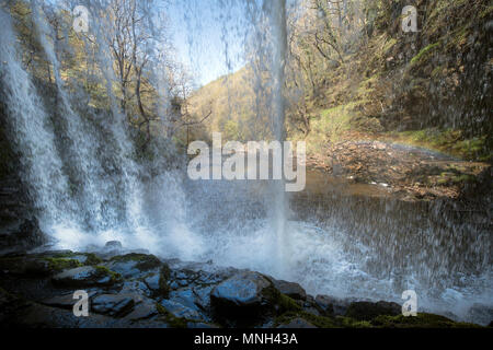 The Four Waterfalls Walk near Pontneddfechan in the Brecon Beacons - curtain of water from behind the Sgwd yr Eira falls (Falls of Snow) on the River  - Stock Photo
