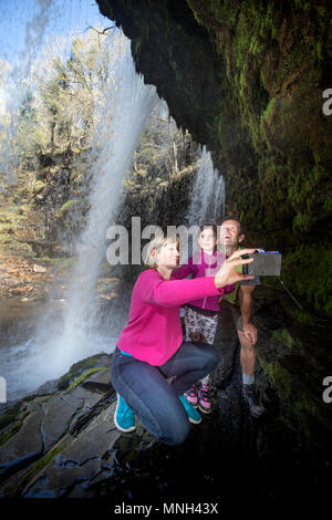 The Four Waterfalls Walk near Pontneddfechan in the Brecon Beacons - a family walk behind the Sgwd yr Eira falls (Falls of Snow) on the River Hepste - Stock Photo