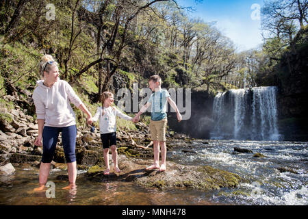 The Four Waterfalls Walk near Pontneddfechan in the Brecon Beacons - a family paddles at the Sgwd yr Eira falls (Falls of Snow) on the River Hepste - Stock Photo
