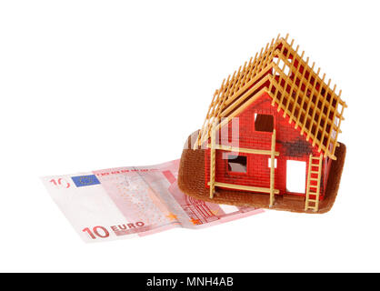 Stockholm, Sweden - November 27, 2017: A small red house being built on a 10 euro banknote isolated on white background. - Stock Photo