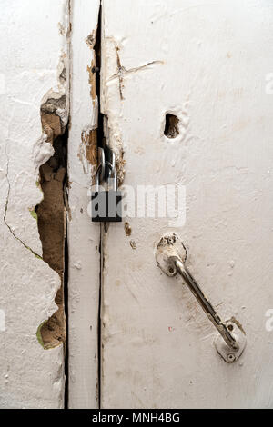Small closed lock on an old door - Stock Photo