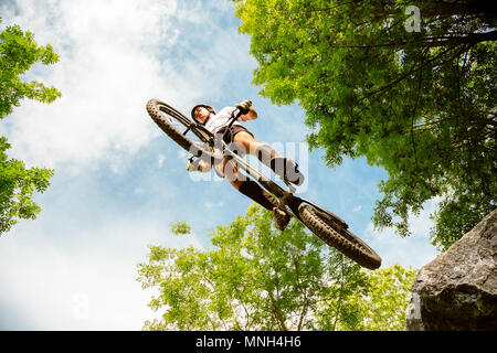 Young cyclist flying with his bycicle from a rock in the forest. Extreme low angle view - Stock Photo
