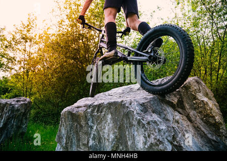 Cyclist legs on a trial bycicle up on a rock at sunset. Concept of extreme sport - Stock Photo