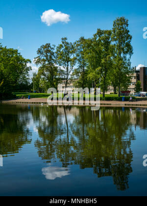 Heriot Watt University campus, Edinburgh, Scotland, United Kingdom, 17th May 2018. People enjoying a sunny lunch break by The Loch on Riccarton Estate of the campus - Stock Photo