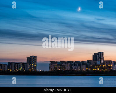 Leith Harbour, Edinburgh, Scotland, United Kingdom, 17th May 2018. UK Weather: An unusual night sky event of a beautifully slender crescent super moon visible just after a glorious sunset, looking across the Entrance Basin harbour towards the high rise apartment buildings of Platinum Point - Stock Photo