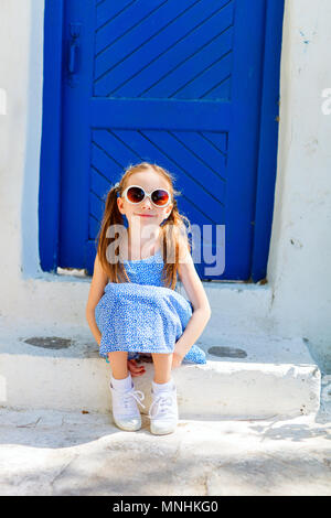 Charming little girl sitting outdoors in front of a blue door at typical greek traditional village on Mykonos Island, Greece, Europe - Stock Photo