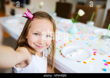 Adorable little girl with princess crown at kids birthday party making selfie - Stock Photo