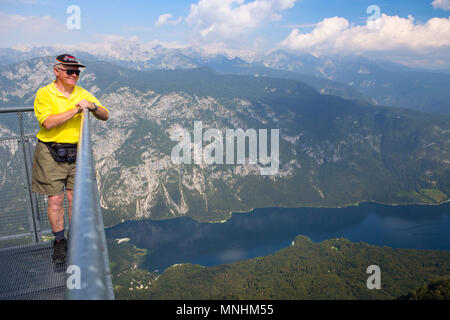 Man enjoying view over lake Bohinj, from mount Vogel, largest permanent lake located in Bohinj Valley of Julian Alps, Triglav National Park, Slovenia - Stock Photo